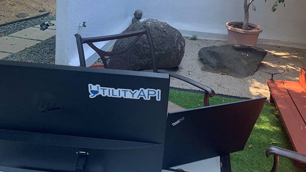 picture of Sean Mazelli's home laptop computer, outside on a pation, with UtilityAPI sticker